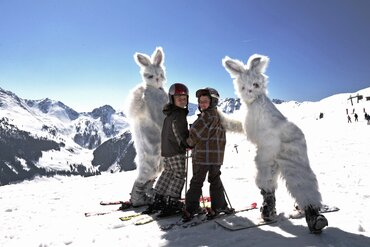 Children with snow hares on a slope in Alpbachtal